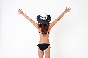 Back of woman in bikini with hat in white isolated background