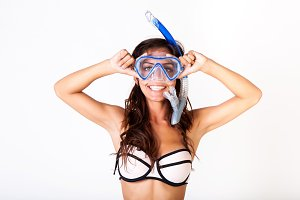 Young woman in bikini posing with snorkel mask on white isolated background