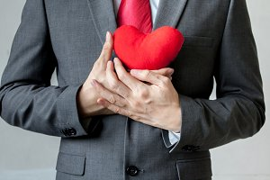 Businessman showing compassion holding red heart onto his chest in his suit - crm, service mind business concept