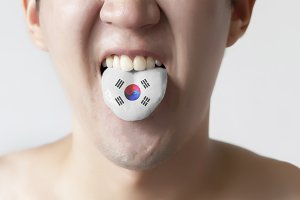 South Korea flag painted in tongue of a man - indicating Korean language and speaking