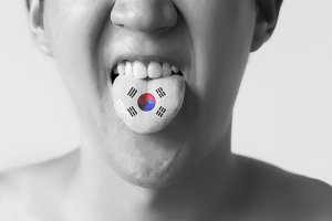 South Korea flag painted in tongue of a man - indicating Korean language and speaking in Black and White