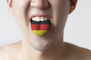 Germany flag painted in tongue of a man - indicating German language and speaking