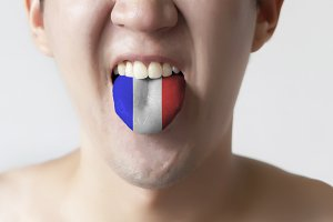 France flag painted in tongue of a man - indicating French language and speaking
