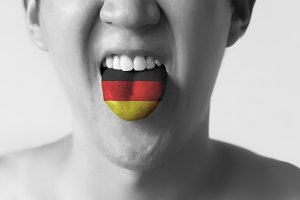 Germany flag painted in tongue of a man - indicating German language and speaking in Black and White