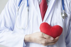 Doctor showing compassion and support holding red heart onto his chest in his coat