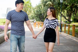 Asian couple holding hands and taking a walk in the green nature