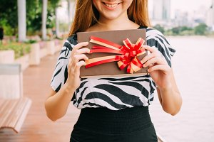 Asian woman receiving a gift from her loved one