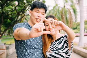 Closeup shot of young loving couple making heart shape with hands in the park