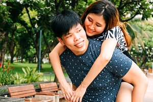 Asian boyfriend carrying his smiling girlfriend in public park
