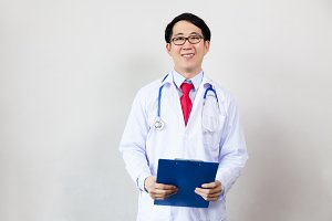 Young Asian medical doctor holding a medical report clipboard on white isolated background