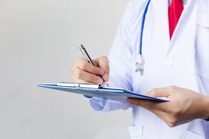 Medical doctor writing prescription on white isolated background (Focus on clipboard)