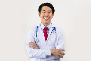 Young Asian male doctor smiling with arms folded having stethoscope on his neck isolated on white background