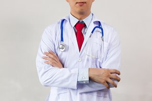 Close-up of male doctor with arms folded having stethoscope on his neck isolated on white background