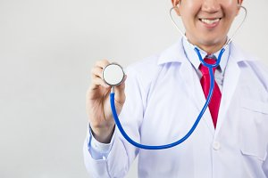 Close-up of smiling male doctor using stethoscope and focusing on stethoscope