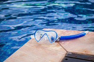 Snorkel mask laying beside the pool with copy space