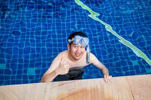 Young Asian man wearing a snorkel mask and smiling by the pool