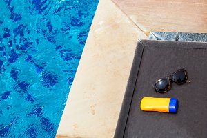 Top view of sunglasses and sun lotion on poolside with copy space - summer concept