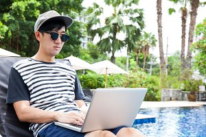 Asian man using a laptop in the pool on vacation - work anywhere and internet work concept