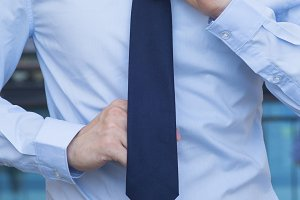 Closeup of Male office worker tying a tie
