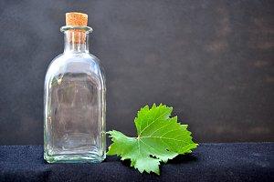 bottle and grapes leaf