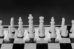 Chess pieces lining up on Chess board on dark background behind