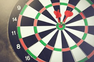 Darts accurately and perfectly hit the winning red spot on board (Focus on tip of the dart) - indicates right targeting, marketing, focus concept