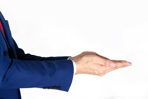 Businessman in blue suit presenting empty palm - it can be used to advertise product on his hands