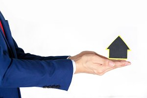 Businessman showing a house shaped sign - property sale and rental concept