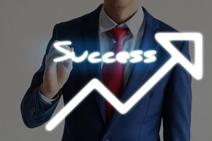Businessman drawing SUCCESS and upward graph arrows forward