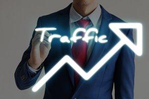 Businessman drawing TRAFFIC and upward graph arrows forward