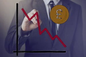 Businessman drawing diagram of Pound Sterling Currency in decline
