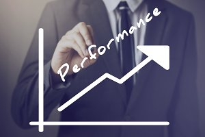 Businessman writing increasing positive Performance chart upward