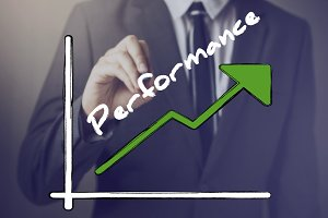 Businessman writing increasing positive Performance chart upward