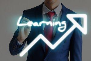 Businessman drawing LEARNING and upward graph arrows forward