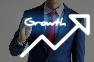 Businessman drawing GROWTH and upward graph arrows forward