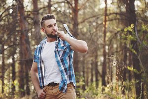 Lumberjack in plaid shirt with an ax
