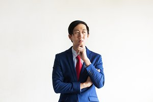 Asian Businessman in professional suit thinking in dramatic tone with copy space