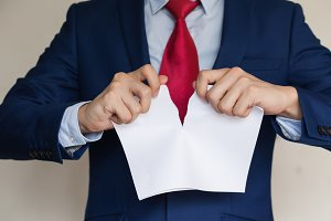 Businessman tearing blank paper apart on white background