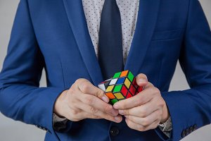 Businessman solving cubic problems - problem solution and making strategic moves concept