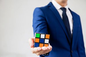 Businessman holding Rubik's cube - business solving problem and brain training concept