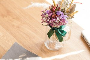 Top view of glass of flowers on wooden background