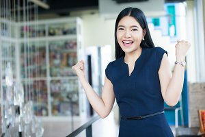 Excited Asian woman raising her arms showing happiness - success and business concept