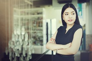 Asian woman having arms folded on office background