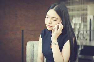 Asian business woman talking on the phone with unhappy or stressful look in office background (Vintage tone)