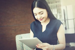 Beautiful Asian woman using a tablet indoor (Vintage tone)