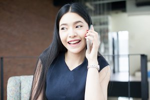 Beautiful Asian woman talking on the phone in office