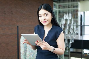 Beautiful Asian woman using a tablet indoor