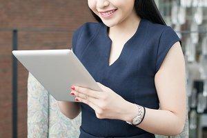 Smiling beautiful Asian woman using smart phone