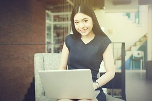 Asian woman sitting and playing a laptop in office background