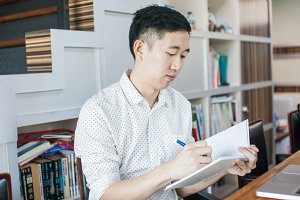 Young casual Asian man sitting and writing on notebook